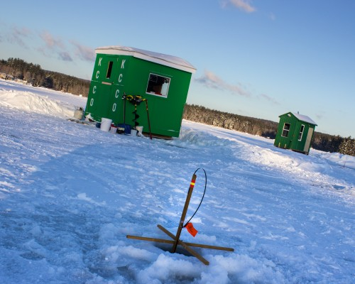 Outside this bob-house is a tip-up.  The crossed pieces keep it above the ice.  At the end of the bent rod is the hook.  When a fish takes the bait, the rod and flag pop up.  Fishermen (and women) can watch from the warmth and comfort of their bob-house.